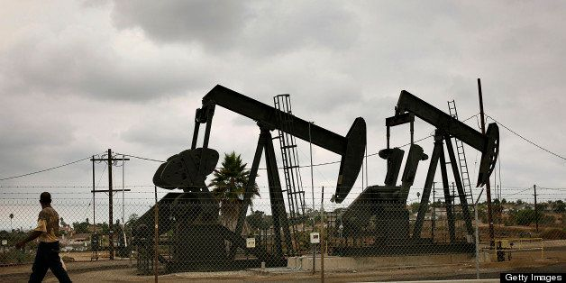 A pedestrian walks past pumpjacks operating at the Inglewood Oil field in Los Angeles, California, U.S., on Thursday, Oct. 19