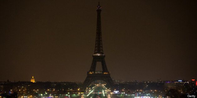 The Eiffel tower is seen before submerging into darkness at 8:30 pm (local time) as part of the Earth...