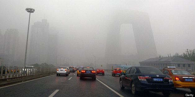 This picture taken on June 5, 2013 shows vehicles under heavy smog in Beijing.  The capital has seen 46 smog days among the 1
