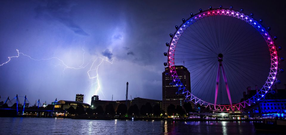 Lightning strikes behind The London Eye in central London which is lighted up in the national colors of red, white and blue t