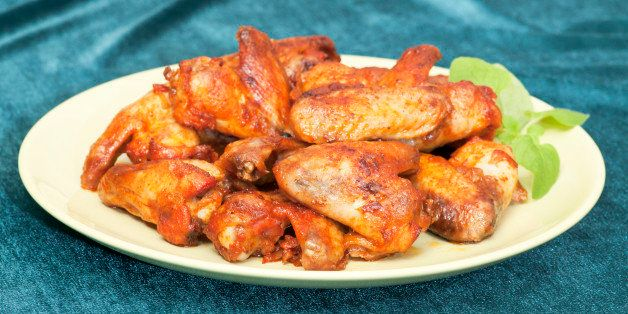 Chicken wings on plate. Freshly baked, selective focus. Green background..
