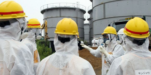 Japan's nuclear watchdog members, including Nuclear Regulation Authority members in radiation protection suits, inspect contaminated water tanks at the Tokyo Electric Power Co (TEPCO) Fukushima Dai-ichi nuclear power plant in the town of Okuma, Fukushima prefecture on August 23, 2013. Japan's nuclear watchdog dispatched an inspection team to the crippled Fukushima plant after workers found a huge toxic water leak and unexplained radiation hotspots. Earlier this week around 300 tonnes of radioactive liquid is believed to have escaped from one of the hundreds of tanks that hold polluted water, some of which was used to cool the broken reactors, in an episode dubbed the most serious in nearly two years. JAPAN OUT AFP PHOTO / JAPAN POOL via JIJI PRESS (Photo credit should read JAPAN POOL/AFP/Getty Images)