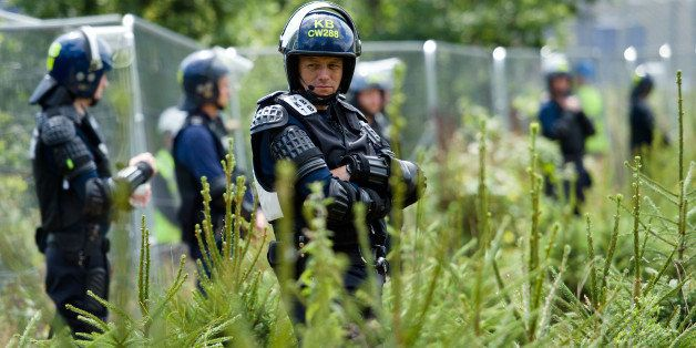 Police officers in body armour line the perimeter fence of the test drill site operated by British energy firm Cuadrilla Reso