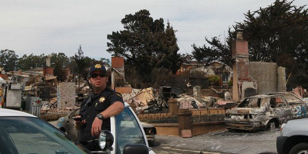 SAN BRUNO, CA - SEPTEMBER 13:  A San Mateo County Sheriff deputy stands guard on a street devastated by fire following a dead