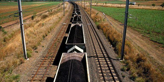coal train on railway tracks in rural landscape