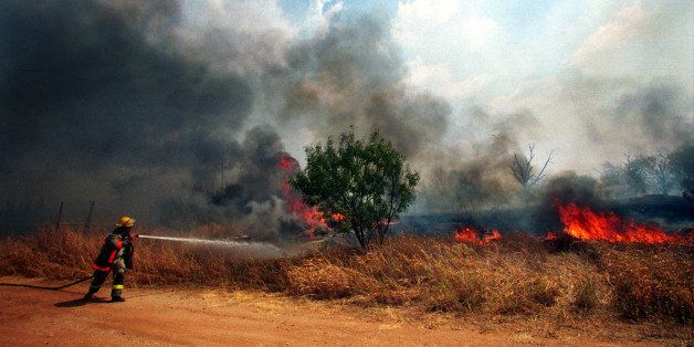 377913 01: A firefighter sprays water on a fast moving grass fire, September 7, 2000 in Ranger, Texas. Forest fires and grass