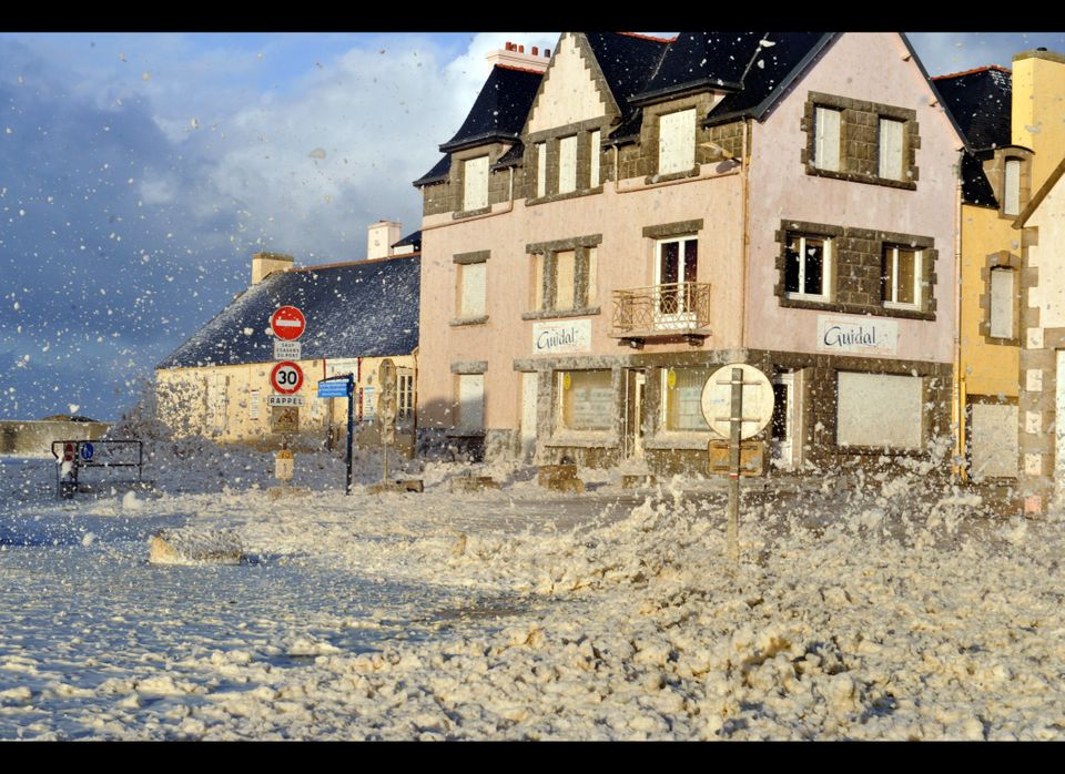 Foam breaks onto the docks of the French northwestern harbour of Saint-Guenole during a severe storm on December 16, 2011. Th