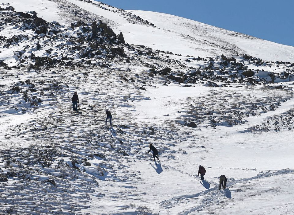 Hikers make their way up the side of a snow-covered mountain at the Continental Divide, elevation 11,990 feet, a day after fr