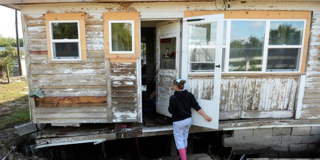 LASALLE, CO - SEPTEMBER 19: Michelle Toubeaux checks out the damage to her home in LaSalle, September 19, 2013. A folding cha