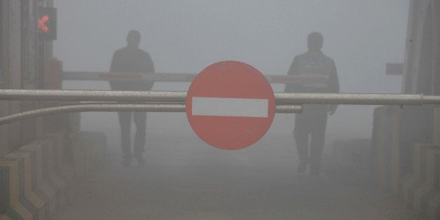 A toll booth is shuttered as heavy smog spreads on a highway as vehicles are forced to wait due to heavy smog in Jilin, north