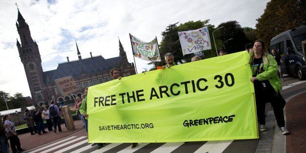 Greenpeace activists and supporters protest during a solidarity march for 30 activists jailed by Russia, from the Russian emb
