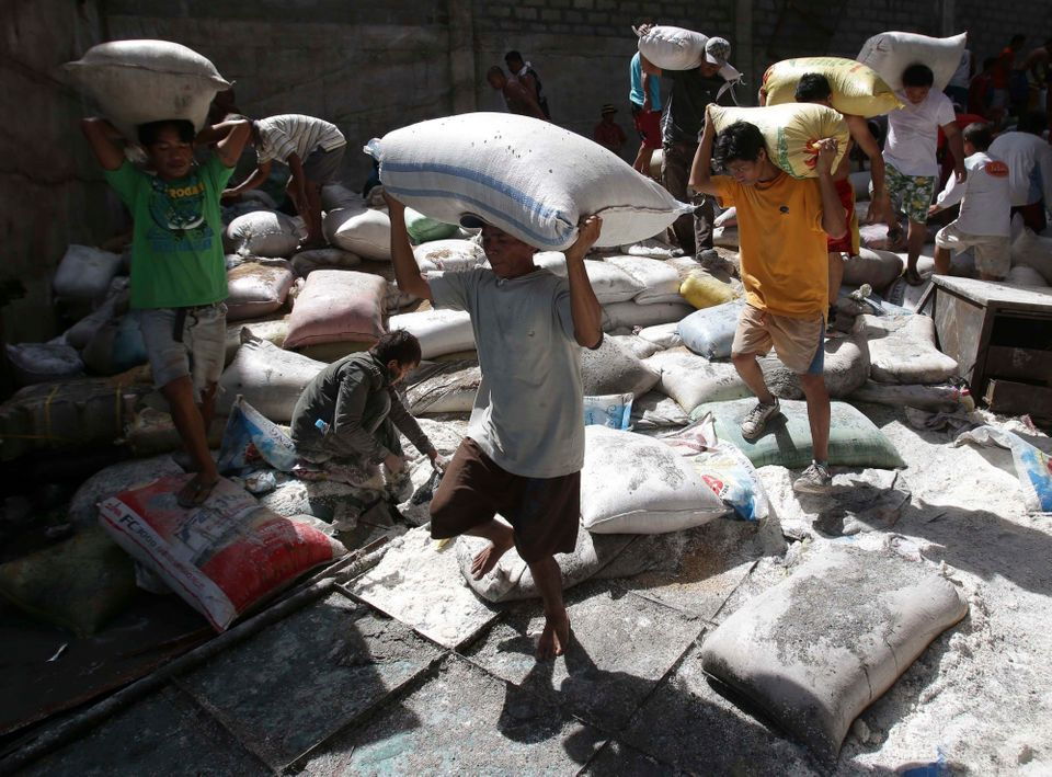 Survivors bring bags of rice from a warehouse which they stormed due to shortage of food at typhoon-ravaged Tacloban city, Le