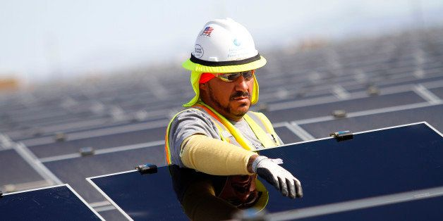A worker installs First Solar Inc. photovoltaic solar panels at the Agua Caliente Solar Project in Yuma County, Arizona, U.S.