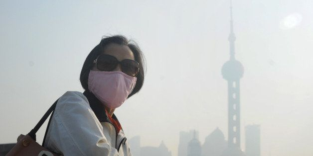 SHANGHAI, CHINA - NOVEMBER 07:  (CHINA OUT) A woman wearing mask walks in highly polluted air at the Bund on November 7, 2013