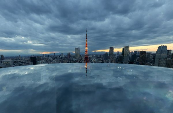 The Tokyo Tower, center, stands amid other buildings as it is reflected on a table at dusk in Tokyo, Japan, on Wednesday, Nov