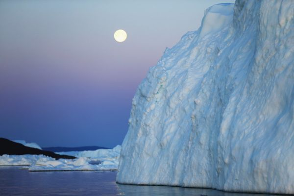 A full moon is seen over an iceberg that broke off from the Jakobshavn Glacier on July 23, 2013 in Ilulissat, Greenland.  As