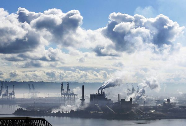 A blue sky begins to emerge from early morning clouds and fog as the Simpson Tacoma Kraft Company pulp and paper mill operate