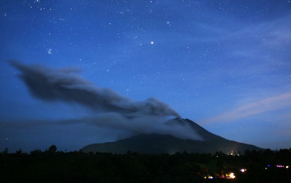 This picture made with slow shutter speed shows Mount Sinabung spewing volcanic ash as seen from Tiga Pancur, North Sumatra,