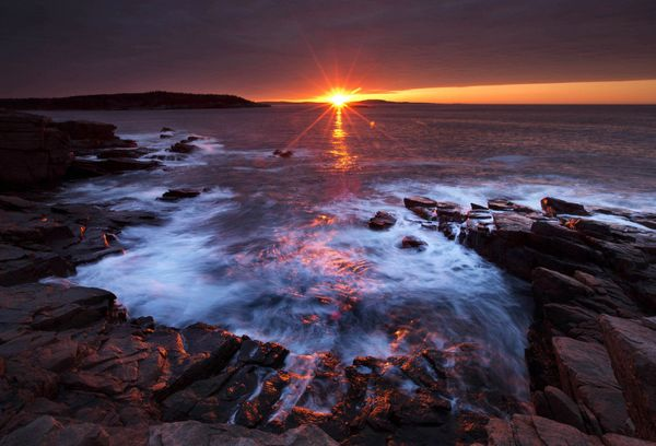The sun's rays strike the rocky coast of Acadia National Park, in Maine, Thursday, May 2, 2013. A federal budget-related dela