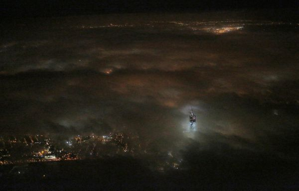 One World Trade Center emerges from the clouds in the night sky in a photo made from a passing airplane, Monday, March 11, 20