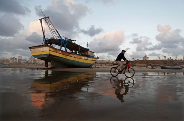A Palestinian man rides a bicycle on the beach of Gaza City during sunset on Tuesday. April 9, 2013. (Hatem Moussa/AP)