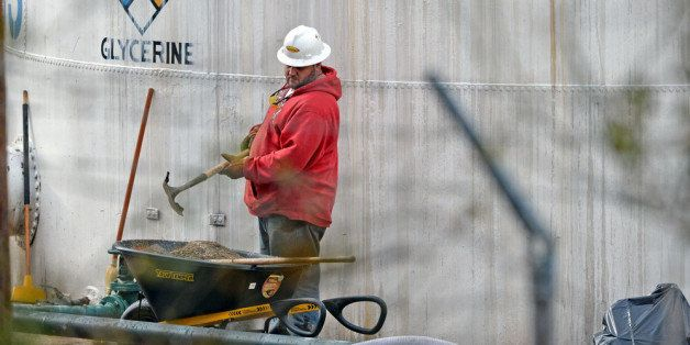 CHARLESTON, WV - JANUARY 10:   An unidentified worker at Freedom Industries shovels NAPA premium oil absorbent on January 10,