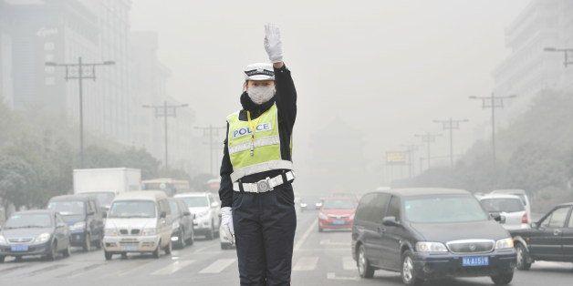XI AN, CHINA - DECEMBER 18:  (CHINA OUT) A traffic policewoman wearing mask directs traffic as heavy smog engulfs the city on