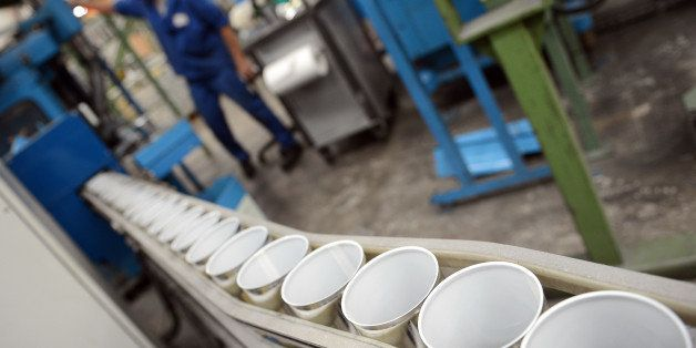 An employee of Massilly, a company which manufatures food metallic packaging, works on a line of cans covered by a polish con