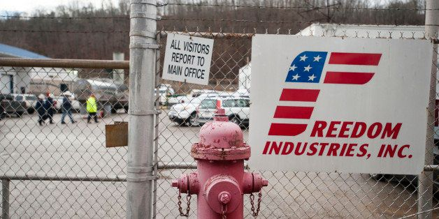 CHARLESTON, WV JANUARY 11, 2014: Workers walk behind the fence at the Freedom Industries building in CharlestonCharleston, W