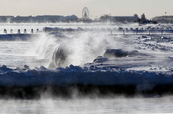 Ice forms as waves crash along the lake shore as Navy Pier's Ferris Wheel is seen in the background Monday, Jan. 27, 2014. (A