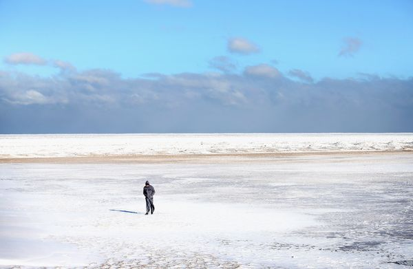 A man walks on ice along the shore of Lake Michigan as storm clouds, which dumped several inches of lake-effect snow on the c