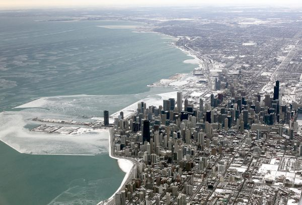 An aerial view shows downtown Chicago surrounded by snow and icy Lake Michigan Thursday, Jan. 30, 2014. (AP Photo/Kiichiro Sa