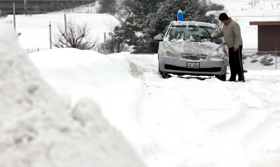 A man clears snow from his car in Rosemont, Ill., Saturday, Feb. 1, 2014. (AP Photo/Nam Y. Huh)