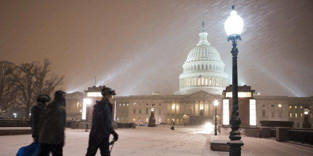 A young man on skis and his friends pass in front of the US Congress building as a heavy snow storm hits Washington D.C. on F