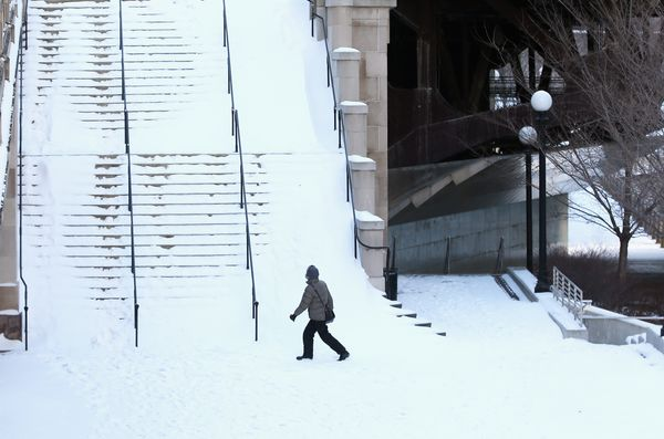 A pedestrian navigates a snow-covered stairway along the Chicago River as temperatures drop below zero January 27. (Photo by
