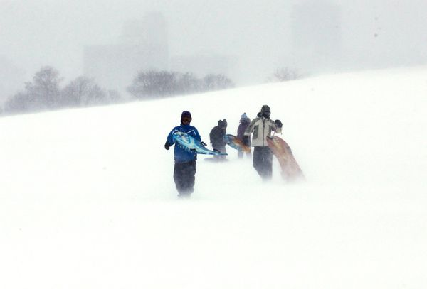 People carry sleds at Montrose Beach Park in Chicago on Sunday, Jan. 5, 2014. (AP Photo/Nam Y. Huh)