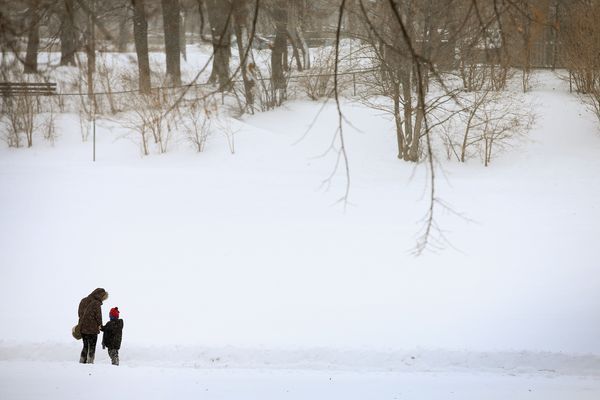 A woman and child walk through a snow-covered field in Humboldt Park on January 2, 2014. (Photo by Scott Olson/Getty Images)