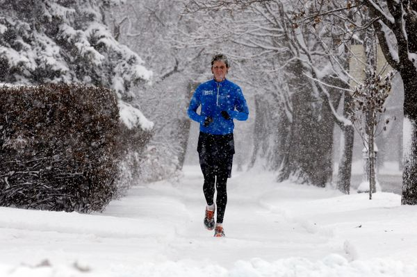 A jogger runs on a snowy sidewalk in Evanston, Ill. on Saturday, Dec. 14, 2013. (AP Photo/Nam Y. Huh)