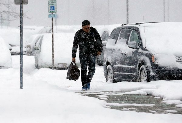 A traveler walks in the economic parking lot at O'Hare International Airport in Chicago, Thursday, Jan. 2, 2014. (AP Photo/Na