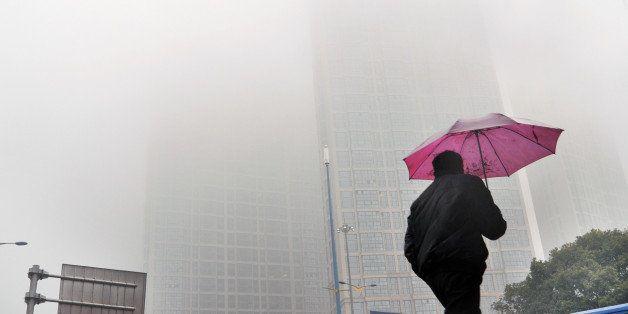 CHANGSHA, CHINA - FEBRUARY 24:  (CHINA OUT) A man holding umbrella walks in the haze on February 24, 2014, in Changsha, Hunan