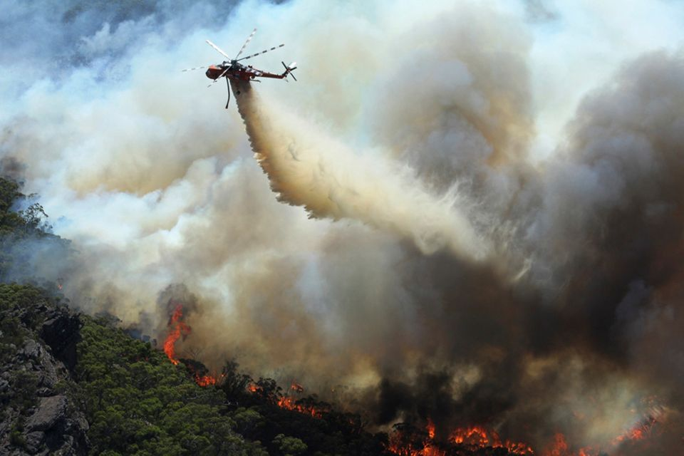 In this Thursday, Jan. 16, 2014 photo released by Victoria Country Fire Authority, a water bomber works over a large fire bur