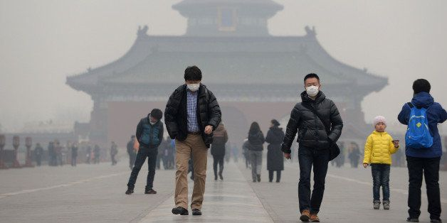 This picture taken on February 24, 2014 shows visitors wearing masks in Temple of Heaven in haze-covered Beijing. Dangerous s