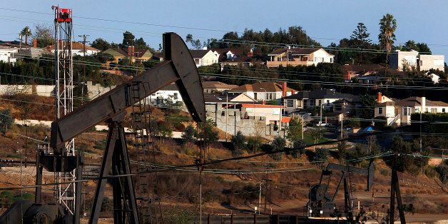 Homes stand while pumpjacks operate near a hydraulic fracturing (fracking) test well at the Inglewood Oil field in Los Angele