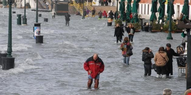 People walk on a flooded quay of the Grand canal of Venice on December 1, 2008. Authorities in the Italian city of Venice iss