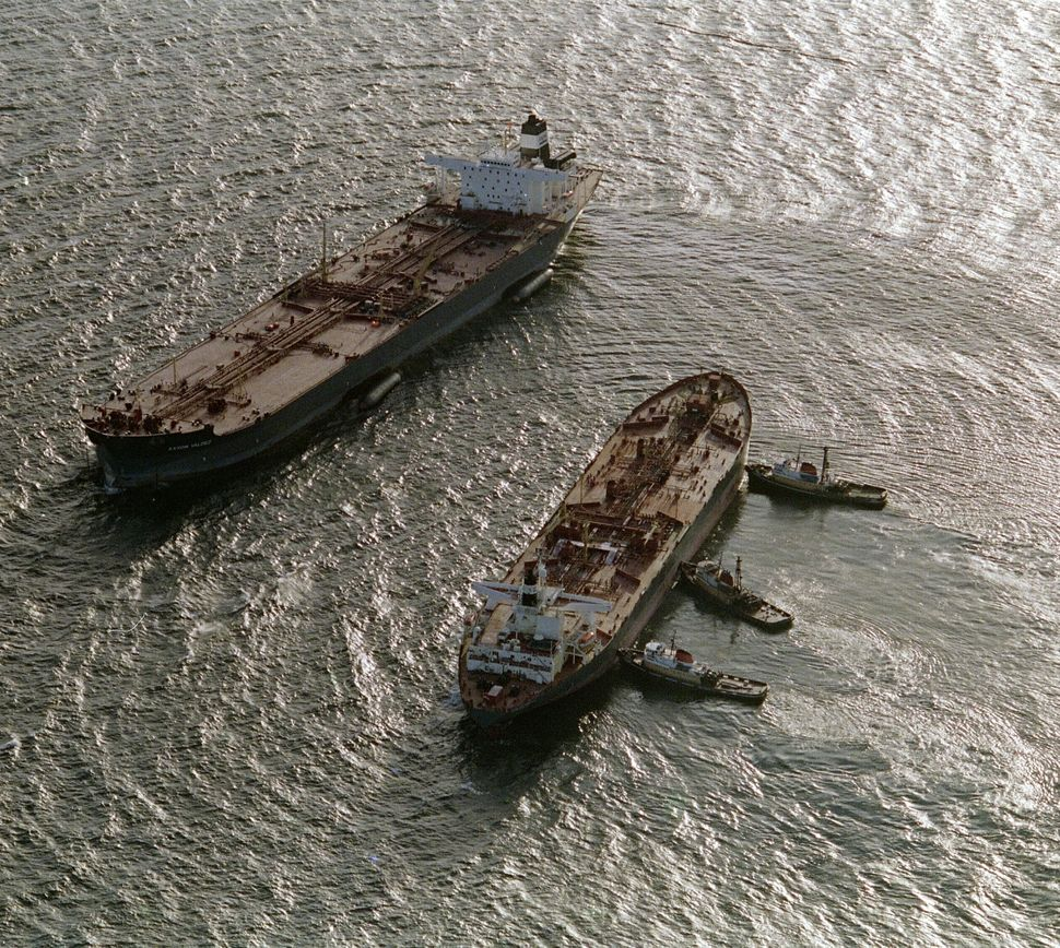 Three tugboats (R) push the oil tanker Exxon San Francisco (C) into place beside the crippled tanker Exxon Valdez (L) in Prin