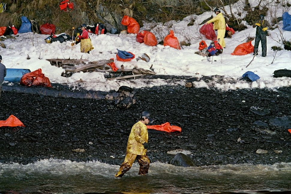 An oil cleanup worker walks through the oily surf at Naked Island on Prince William Sound on April 2, 1989 as beach cleanup g