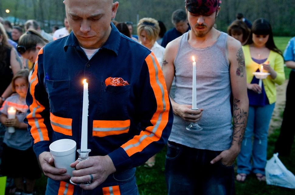 Thomas Jones (L), a local coal miner, participates in a candlelight vigil in Whitesville, West Virginia on April 7, 2010. AFP