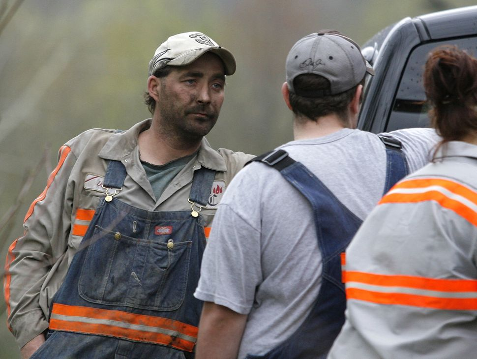 Brian Lemon (L), a Massey Energy miner at the Blackstone Mine, talks with other miners near the Upper Big Branch Mine on Apri