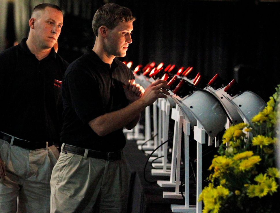 Lights on helmets are turned on during a memorial service for the miners killed in the Upper Big Branch Mine, in Beckley, W.V