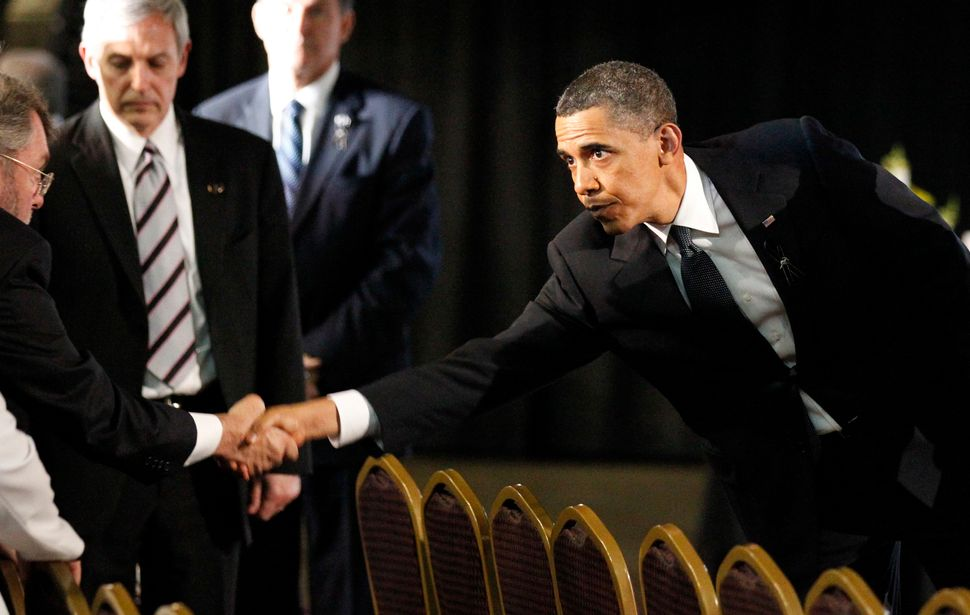 President Barack Obama, right, reaches to shake hands with a relative at a memorial service for the miners killed in the Uppe